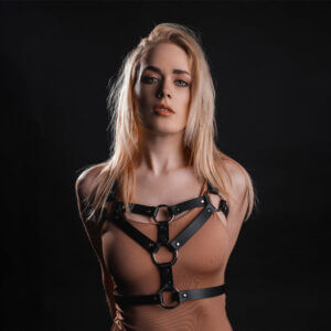 Young lady in black leather chest harness